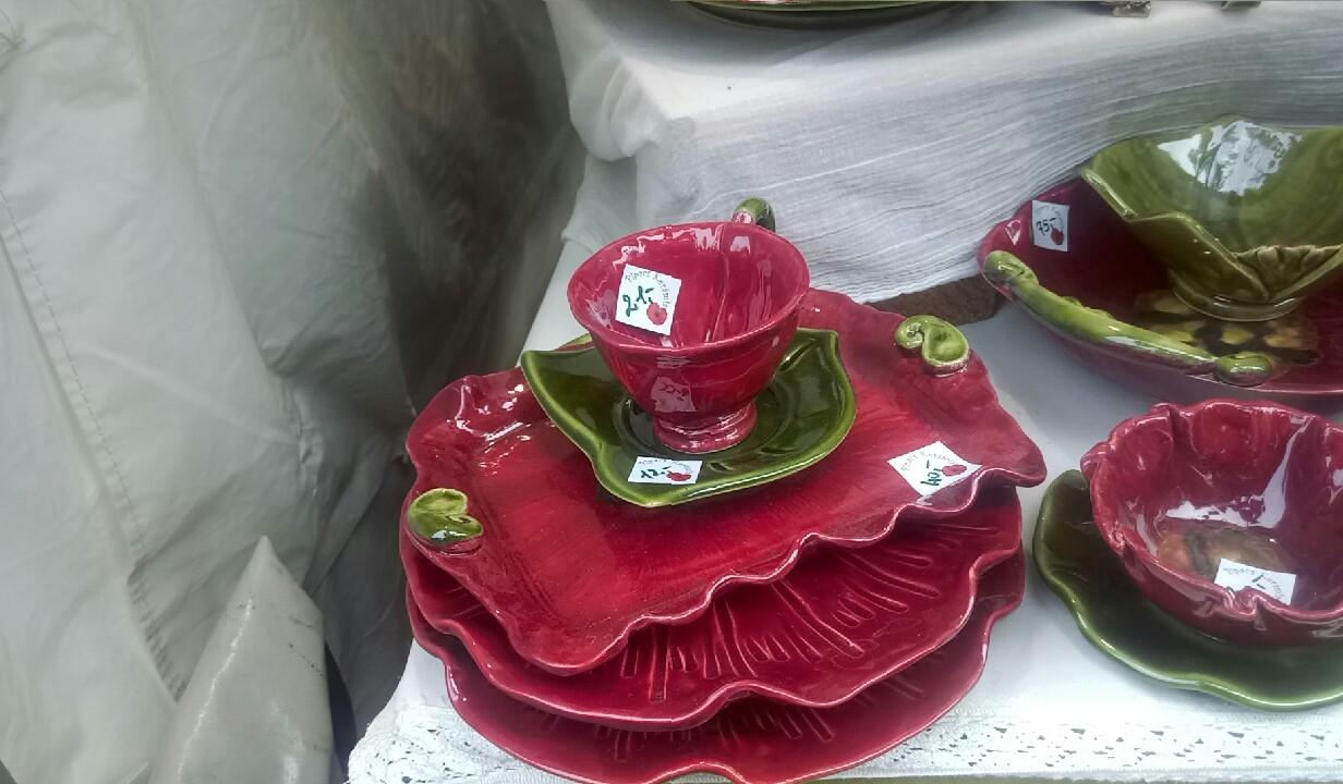 Cană, farfurii și boluri roșii și verzi, cu forme ce amintesc de frunze și flori.