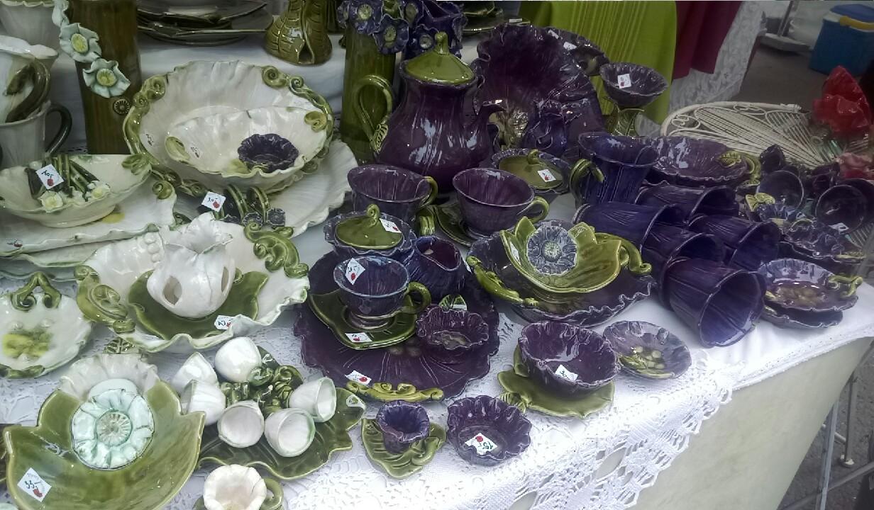 Căni, farfurii și boluri albe, verzi și mov închis, cu forme ce amintesc de frunze și flori.