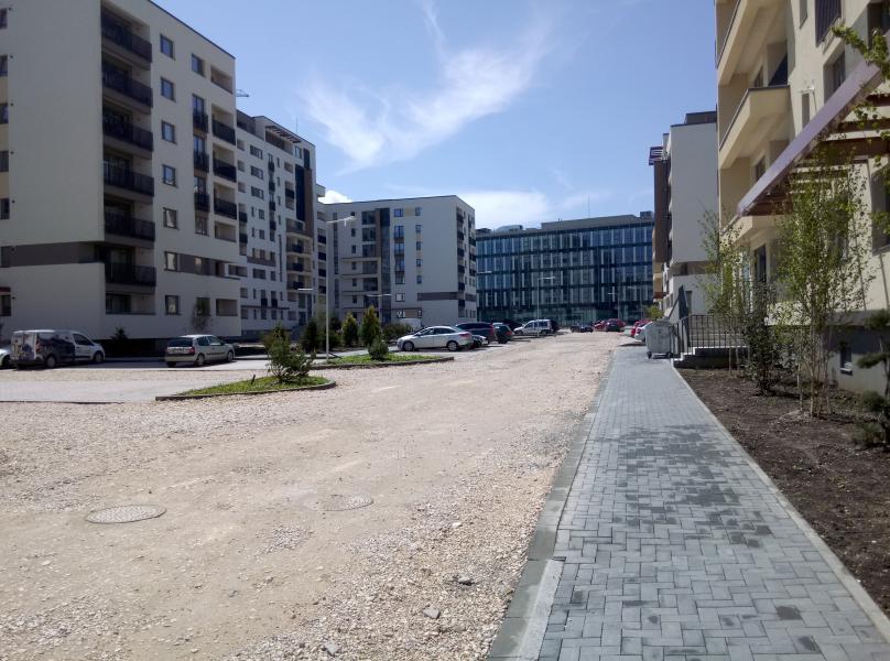 Poză Avantgarden 2. Un drum neasfaltat, un trotuar făcut, vreun metru jumătate sau doi față de bloc unde sunt plantați copaci, încă mici. Se văd tufe pe petice de iarbă lângă parcări.