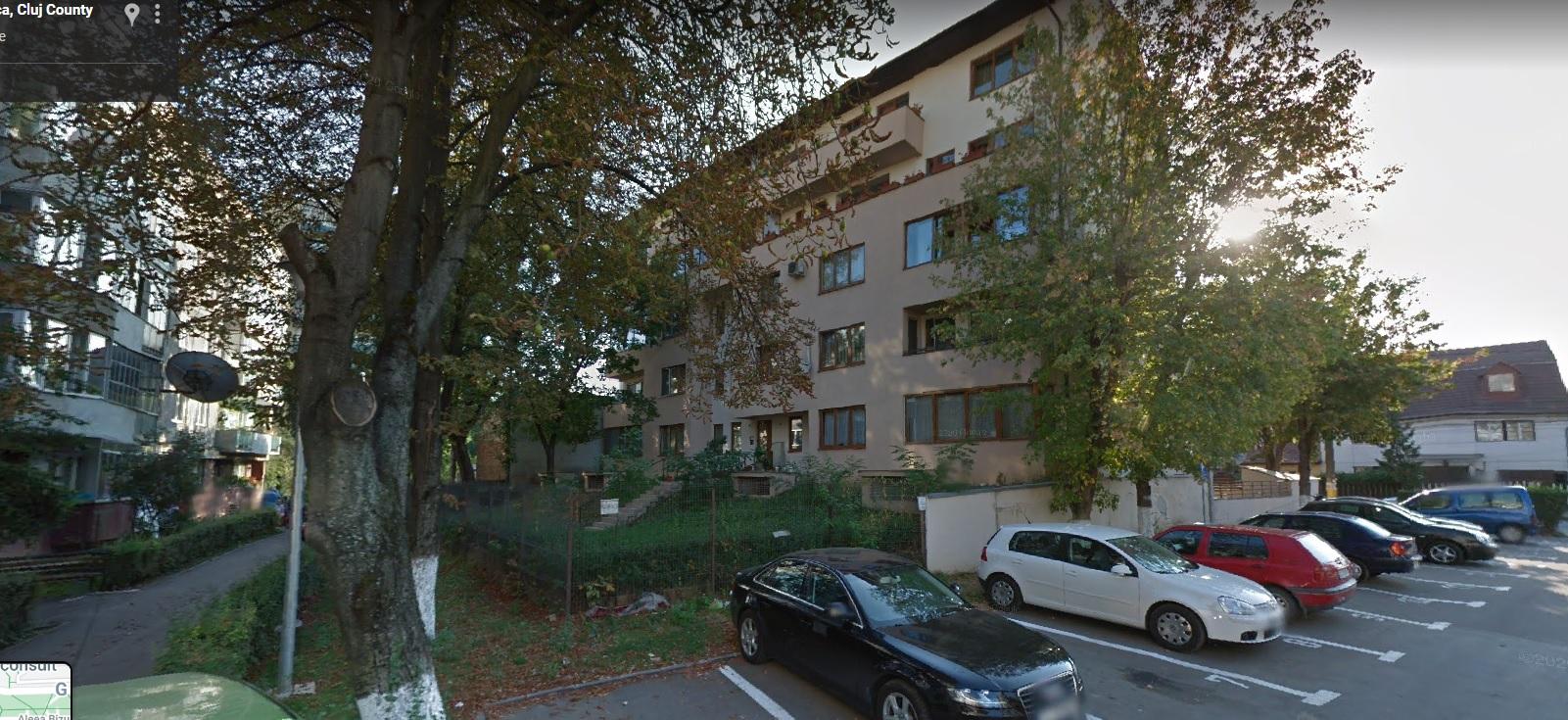 Poză cu două blocuri, unul în stânga, altul în dreapta. Între ele, o zonă verde și un șir de copaci. Se vede și o parcare.